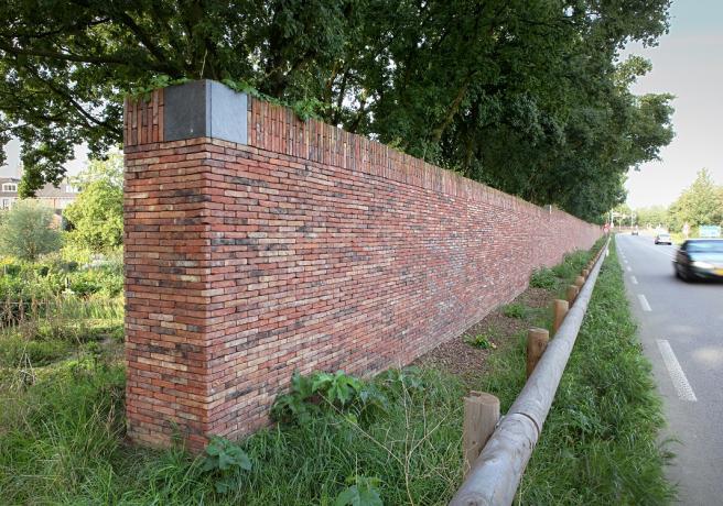 Keerwand beplakt met steenstrips langs N317 bij Doesburg